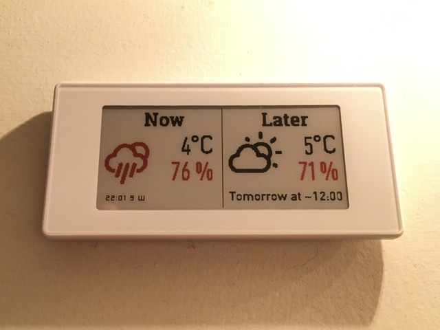 A rectangular e-paper display, the left half showing current weather and the right half showing upcoming rainy weather in red.